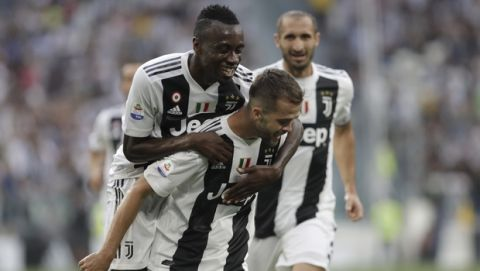 Juventus' Miralem Pjanic, bottom, celebrates with teammate Juventus' Blaise Matuidi after scoring the opening goal of the game during the Serie A soccer match between Juventus and Lazio at the Allianz Stadium in Turin, Italy, Saturday, Aug. 25, 2018. (AP Photo/Luca Bruno)