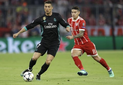Real Madrid's Cristiano Ronaldo, left, and Bayern's James challenge for the ball during the semifinal first leg soccer match between FC Bayern Munich and Real Madrid at the Allianz Arena stadium in Munich, Germany, Wednesday, April 25, 2018. (AP Photo/Matthias Schrader)