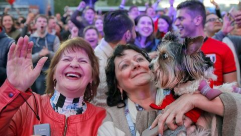 A small dog is startled as fans celebrate after Russia scored the third goal during the opening match of the 2018 soccer World Cup, between Russia and Saudi Arabia, in the fan zone in Yekaterinburg, Russia, Thursday, June 14, 2018. (AP Photo/Vadim Ghirda)