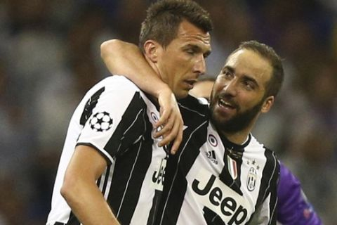 Juventus' Mario Mandzukic, left, celebrates with Juventus' Gonzalo Higuain after scoring during the Champions League final soccer match between Juventus and Real Madrid at the Millennium stadium in Cardiff, Wales Saturday June 3, 2017. (AP Photo/Dave Thompson)