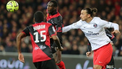 Paris Saint Germain's forward Zlatan Ibrahimovic of Sweden, right, challenges for the ball with Guingamp's french defender Benjamin Brou Angoua during their League One soccer match, in Guingamp, western France, Sunday, Dec. 14 , 2014. Guingamp won 1-0. (AP Photo/David Vincent)