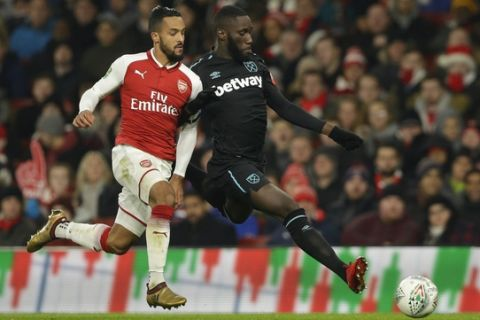 Arsenal's Theo Walcott, left, vies for the ball with West Ham United's Arthur Masuaku during the English League Cup quarterfinal soccer match between Arsenal and West Ham United at the Emirates stadium in London, Tuesday, Dec. 19, 2017. (AP Photo/Alastair Grant)