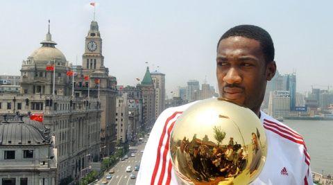 Gilbert Arenas of the Washington Wizards holds the NBA championship trophy with the line of old buildings known as the Bund in the background in Shanghai, Sunday, May 23, 2004. The trophy is being taken on a tour of U.S. cities, as well as Beijing, Shanghai, London and Munich, to promote the NBA before being delivered to Game 1 of the NBA finals. (AP Photo/Eugene Hoshiko)