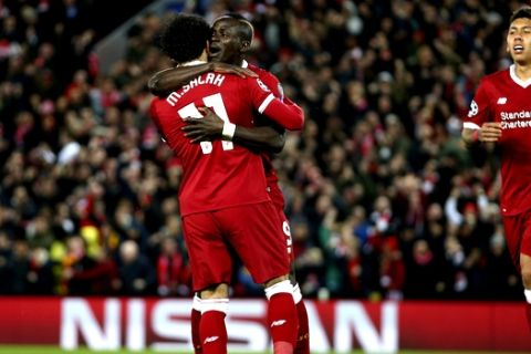 Liverpool's Sadio Mane celebrates with Mohamed Salah, left, and Roberto Firmino, right, after scoring his side's third goal during the Champions League semifinal, first leg, soccer match between Liverpool and AS Roma at Anfield Stadium, Liverpool, England, Tuesday, April 24, 2018. (AP Photo/Dave Thompson)