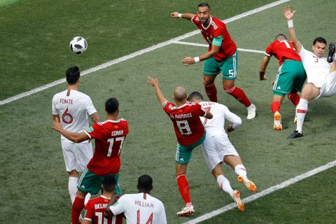 Portugal's Cristiano Ronaldo, center, heads the ball to score the opening goal during the group B match between Portugal and Morocco at the 2018 soccer World Cup in the Luzhniki Stadium in Moscow, Russia, Wednesday, June 20, 2018. (AP Photo/Victor Caivano)