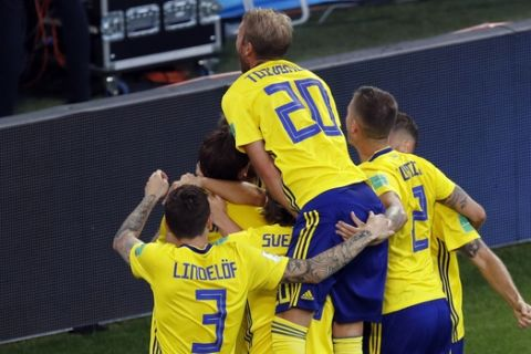 Sweden's Andreas Granqvist celebrates with teammates after scoring his side's second goal on a penalty during the group F match between Mexico and Sweden, at the 2018 soccer World Cup in the Yekaterinburg Arena in Yekaterinburg , Russia, Wednesday, June 27, 2018. (AP Photo/Efrem Lukatsky)