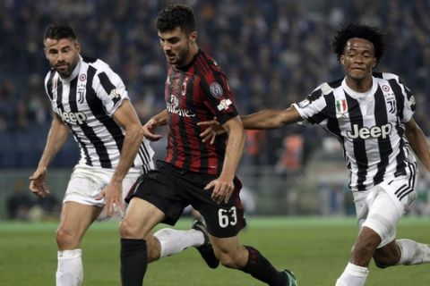 AC Milan's Patrick Cutrone, center, is challenged by Juventus' Andrea Barzagli, left, and Juventus' Juan Cuadrado during the Italian Cup final soccer match between Juventus and AC Milan, at the Rome Olympic stadium, Wednesday, May 9, 2018. (AP Photo/Gregorio Borgia)