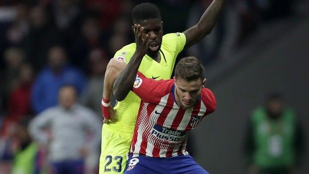 Athletico Madrid's Nikola Kalinic, front, duels for the ball with Barcelona's Samuel Umtiti during a Spanish La Liga soccer match between Atletico Madrid and FC Barcelona at the Metropolitano stadium in Madrid, Saturday, Nov. 24, 2018. (AP Photo/Manu Fernandez)