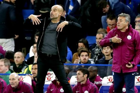 Manchester City coach Josep Guardiola. left, and coaching staff member Domenec Torrent, right, gesture during the English Premier League soccer match between Chelsea and Manchester City at Stamford Bridge stadium in London, Saturday, Sept. 30, 2017. (AP Photo/Frank Augstein)