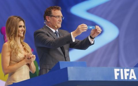 """FIFA Secretary General Jerome Valcke holds up the slip showing """"Mexico"""" next to presenter Fernanda Lima during the draw for the 2014 World Cup at the Costa do Sauipe resort in Sao Joao da Mata, Bahia state, December 6, 2013. The 2014 World Cup finals will be held in Brazil from June 12 through July 13.  REUTERS/Paulo Whitaker (BRAZIL  - Tags: SPORT SOCCER SPORT SOCCER WORLD CUP)"""
