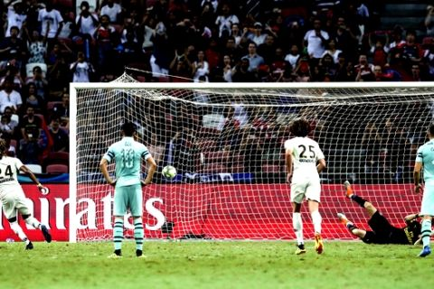 Paris Saint-Germain's Christopher Nkunku, left, scores a penalty during the International Champions Cup match between Arsenal and Paris Saint-Germain in Singapore, Saturday, July 28, 2018. (AP Photo/Yong Teck Lim)