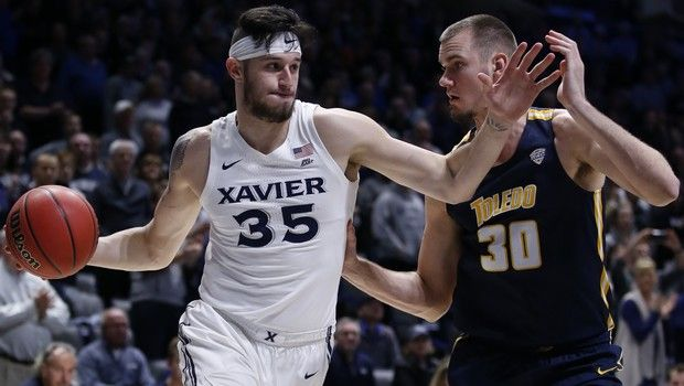 Xavier forward Zach Hankins (35) drives against Toledo center Luke Knapke (30) during the first half of a first round basketball game of the National Invitation Tournament, Wednesday, March 20, 2019, in Cincinnati. (AP Photo/Gary Landers)