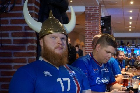 Iceland soccer fans in a bar in Reykjavik, Iceland, Friday, Dec. 1, 2017, watch the 2018 soccer World Cup draw taking part in Moscow. Argentina will be the opponent for Icelandâs debut as the smallest nation ever to play at a World Cup finals tournament. (AP Photo/David Keyton)