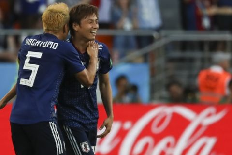 Japan's Takashi Inui, right, celebrates with teammate Yuto Nagatomo after scoring his side's first goal during the group H match between Japan and Senegal at the 2018 soccer World Cup at the Yekaterinburg Arena in Yekaterinburg , Russia, Sunday, June 24, 2018. (AP Photo/Eugene Hoshiko)