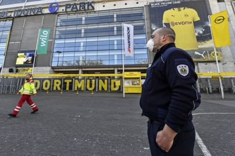 Security with face masks stand in front of the Signal Iduna Park, Germany's biggest stadium of Bundesliga soccer club Borussia Dortmund, where a temporary coronavirus treatment center opened today in Dortmund, Germany, Saturday, April 4, 2020. Instead of the originally scheduled today football clash between Dortmund and Bayern, parts of the stadium were turned into a medical center for outpatient treatment and consultation. The new coronavirus causes mild or moderate symptoms for most people, but for some, especially older adults and people with existing health problems, it can cause more severe illness or death. (AP Photo/Martin Meissner)