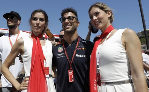 Red Bull driver Daniel Ricciardo of Australia poses with two models during the autographs session in the pit lane at the Monaco racetrack, in Monaco, Friday, May 25, 2018. The Formula one race will be held on Sunday. (AP Photo/Luca Bruno)