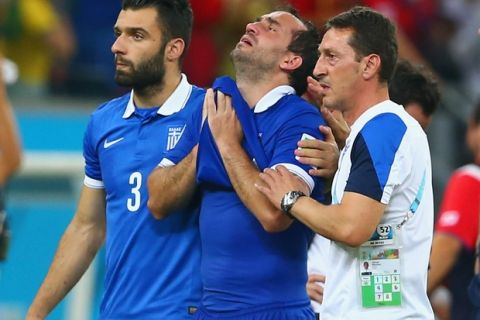 RECIFE, BRAZIL - JUNE 29: Theofanis Gekas of Greece (C) is consoled by teammate Giorgos Tzavellas after being defeated by Costa Rica in a penalty shootout during the 2014 FIFA World Cup Brazil Round of 16 match between Costa Rica and Greece at Arena Pernambuco on June 29, 2014 in Recife, Brazil.  (Photo by Quinn Rooney/Getty Images)