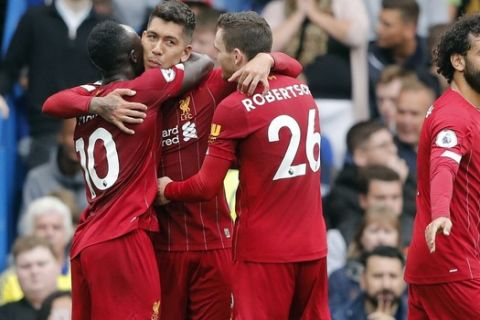Liverpool's Roberto Firmino, center, celebrates with teammates Sadio Mane, left, and Andrew Robertson after scoring his side's second goal during the British Premier League soccer match between Chelsea and Liverpool, at the Stamford Bridge Stadium, London, Sunday, Sept. 22, 2019. (AP Photo/Frank Augstein)
