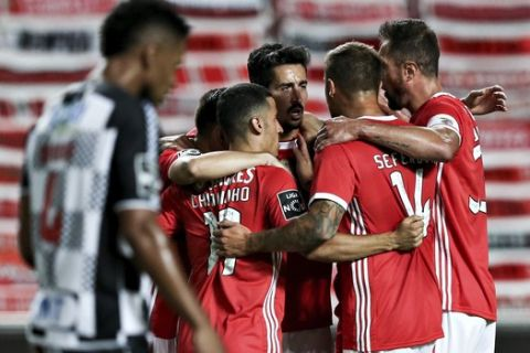 Benfica's Andre Almeida, center, celebrates after scoring the opening goal during the Portuguese League soccer match between Benfica and Boavista at the Luz stadium in Lisbon, Portugal, Saturday, July 4, 2020. The Portuguese League soccer matches are being played without spectators because of the coronavirus pandemic. (Manuel de Almeida/Pool via AP)