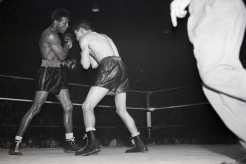 26 Jun 1947, Cleveland, Ohio, USA --- Original caption: 6/26/1947-Cleveland, OH:- Sugar Ray Robinson (l) misses with a right to Doyle's head in the 6th round of their fight at the arena Tuesday. Doyle is seen recoiling from the punch. In the 8th round, Robinson hit the Los Angeles boy a hard left, knocking him out. The unconscious fighter was removed to the hospital for an emergency brain operation but died 17 hours after his knockout. The coroner called the cause of death a cerebral hemorrhage. --- Image by © Bettmann/CORBIS