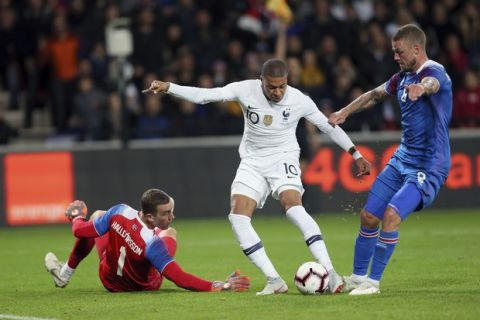 France's Kylian Mbappe, center, challenges for the ball with Iceland's goalkeeper Hannes Halldorsson, left, and Ragnar Sigurdsson, right, during a friendly soccer match between France and Iceland, in Guingamp, western France, Thursday, Oct. 11, 2018. (AP Photo/David Vincent)