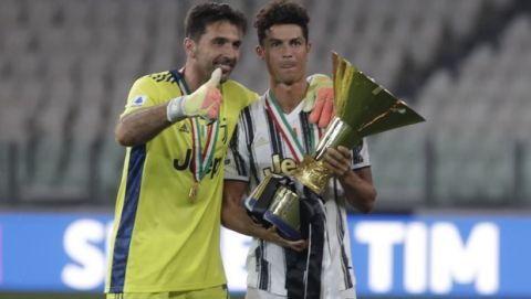 Juventus' Cristiano Ronaldo, right, and Juventus' goalkeeper Gianluigi Buffon hold the trophy as Juventus players celebrate winning an unprecedented ninth consecutive Italian Serie A soccer title, at the end of the a Serie A soccer match between Juventus and Roma, at the Allianz stadium in Turin, Italy, Saturday, Aug.1, 2020. (AP Photo/Luca Bruno)