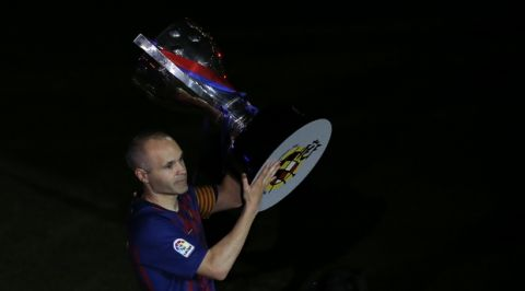 FC Barcelona's Andres Iniesta holds the Spanish La Liga trophy after the Spanish La Liga soccer match between FC Barcelona and Real Sociedad at the Camp Nou stadium in Barcelona, Spain, Sunday, May 20, 2018. (AP Photo/Manu Fernandez)