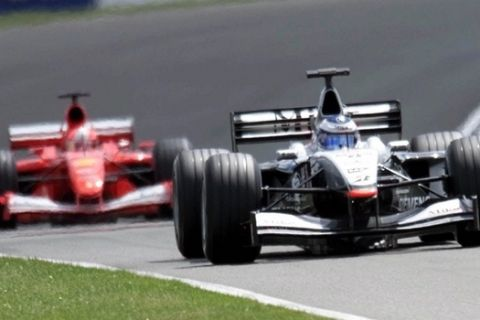 Finland's Mika Hakkinen, in his McLaren, leads Germany's Michael Schumacher, in his Ferrari, during the British Grand Prix being held at Silverstone, England Sunday, July 15, 2001. Mika Hakkinen prevented Michael Schumacher from making history by beating him Sunday in the British Grand Prix. (AP Photo/Max Nash)