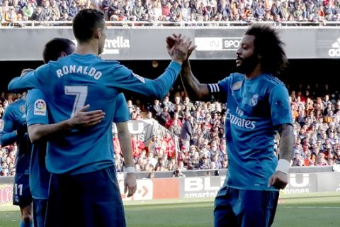 Real Madrid's Cristiano Ronaldo, 2nd right, is congratulated by teammate Real Madrid's Marcelo, right, after scoring, during the Spanish La Liga soccer match between Valencia and Real Madrid at the Mestalla stadium in Valencia, Spain, Saturday, Jan. 27, 2018. (AP Photo/Alberto Saiz)