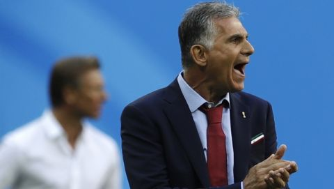 Iran head coach Carlos Queiroz, right, and Morocco coach Herve Renard, left, look at the players during the group B match between Morocco and Iran at the 2018 soccer World Cup in the St. Petersburg Stadium in St. Petersburg, Russia, Friday, June 15, 2018. (AP Photo/Themba Hadebe)