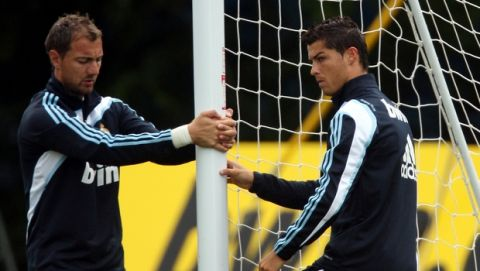 Real Madrid's Cristiano Ronaldo, right, is seen stretching with teammate Jerzy Dudek, left, during a training session at their training camp in Maynooth, Ireland, Tuesday July 14, 2009. Real Madrid is in Ireland for pre-season training and a friendly soccer match against Shamrock Rovers on Monday. (AP Photo/Scott Heppell)