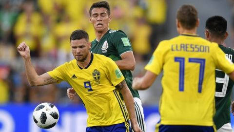 Sweden's Marcus Berg, left, and Mexico's Hector Moreno challenge for the ball Mexico's Hector Moreno during the group F match between Mexico and Sweden, at the 2018 soccer World Cup in the Yekaterinburg Arena in Yekaterinburg , Russia, Wednesday, June 27, 2018. (AP Photo/Martin Meissner)