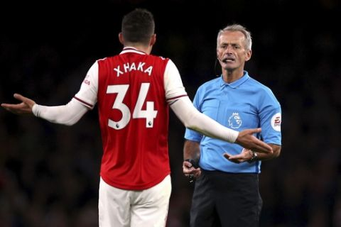 Arsenal's Granit Xhaka speaks to referee Martin Atkinson during the English Premier League soccer match at the Emirates Stadium, London, Sunday Oct. 27, 2019. (Nigel French/PA via AP)