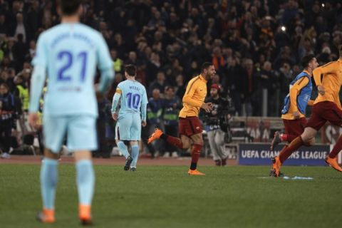 Barcelona's Lionel Messi, second left, walks off the pitch as Roma players celebrate reaching the semifinals during the Champions League quarterfinal second leg soccer match between between Roma and FC Barcelona, at Rome's Olympic Stadium, Tuesday, April 10, 2018. (AP Photo/Gregorio Borgia)