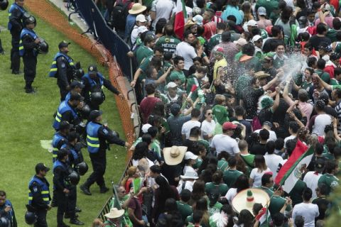 Fans spray foam in the air during the celebration of Mexico's 2018 World Cup win over Germany at the Angel of Independence in Mexico City, Sunday, June 17, 2018. Mexico won it's first match against Germany 1-0. (AP Photo/Anthony Vazquez)