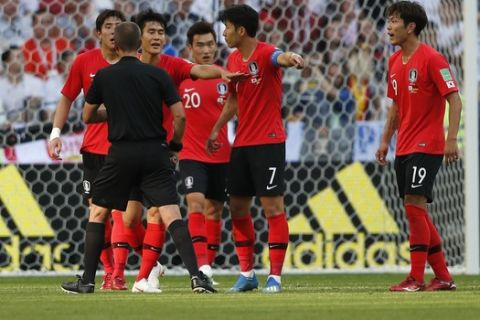 Referee Mark Geiger speaks with South Korea players during the group F match between South Korea and Germany, at the 2018 soccer World Cup in the Kazan Arena in Kazan, Russia, Wednesday, June 27, 2018. (AP Photo/Frank Augstein)