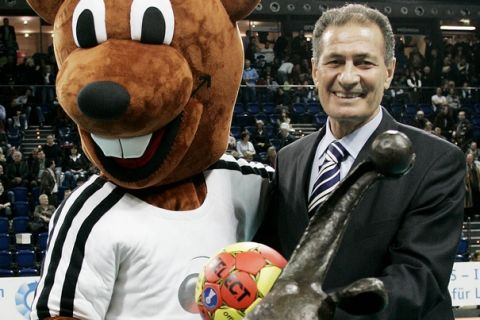 """Egypt's Hassan Mustafa Mussa, President of the International Handball Federation (IHF) displays with the championships' mascot """"Hanniball"""" the trophy at the Ostseehalle in Kiel, northern Germany, on Wednesday, Dec. 13, 2006. The Handball World Championships will be held from Jan. 19 until Feb. 4, 2007 in Germany. (AP Photo/Heribert Proepper)"""