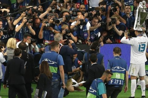 Real Madrid's Cristiano Ronaldo, right, poses with the trophy in front of fans and photographers after the Champions League Final soccer match between Real Madrid and Liverpool at the Olimpiyskiy Stadium in Kiev, Ukraine, Saturday, May 26, 2018. Madrid defeated Liverpool by 3-1. (AP Photo/Darko Vojinovic)