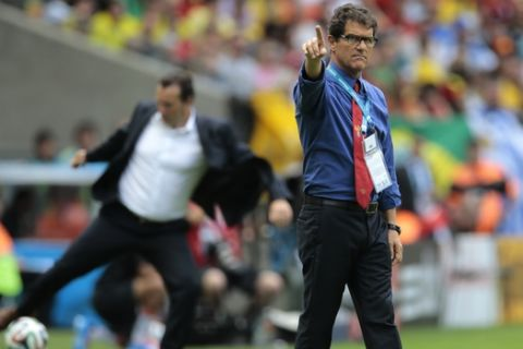 Russia's head coach Fabio Capello gestures as Belgium's head coach Marc Wilmots, left, kicks a ball in the background, during the group H World Cup soccer match between Belgium and Russia at the Maracana stadium in Rio de Janeiro, Brazil, Sunday, June 22, 2014. (AP Photo/Ivan Sekretarev)