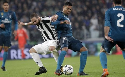 Juventus' Gonzalo Higuain, left, and Real Madrid's Casemiro challenge for the ball during the Champions League, round of 8, first-leg soccer match between Juventus and Real Madrid at the Allianz stadium in Turin, Italy, Tuesday, April 3, 2018. (AP Photo/Luca Bruno)