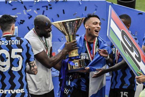Οι Ρομελού Λουκακού και Λαουτάρο Μαρτίνες κρατούν στα χέρια τους το τρόπαιο της πρωταθλήτριας Ιταλίας για τη σεζόν 2020-21, που κατακτήθηκε από την Ίντερ (23 Μαΐου 2021)
