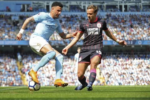 Manchester City's Kyle Walker, left, and Huddersfield's Chris Lowe vie for the ball during the English Premier League soccer match between Manchester City and Huddersfield Town at Etihad stadium in Manchester, England, Sunday, May 6, 2018. (AP Photo/Rui Vieira)