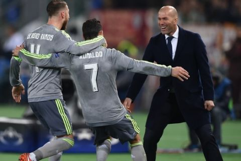 Real Madrid's Portuguese forward Cristiano Ronaldo (C) celebrates with Real Madrid's defender Sergio Ramos and Real Madrid's French coach Zinedine Zidane after scoring during the UEFA Champions League football match AS Roma vs Real Madrid on Frebruary 17, 2016 at the Olympic stadium in Rome.     AFP PHOTO / ALBERTO PIZZOLI / AFP / ALBERTO PIZZOLI        (Photo credit should read ALBERTO PIZZOLI/AFP/Getty Images)