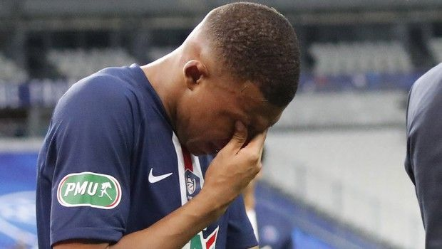 PSG's Kylian Mbappe holds his eyes after being tackled during the French Cup soccer final match between Paris Saint Germain and Saint Etienne at Stade de France stadium, in Saint Denis, north of Paris, Friday July 24, 2020. (AP Photo/Francois Mori)