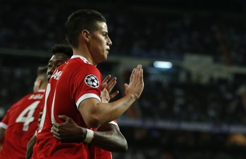 Bayern's James, front, celebrates with teammate David Alaba after scoring his side's second goal during the Champions League semifinal second leg soccer match between Real Madrid and FC Bayern Munich at the Santiago Bernabeu stadium in Madrid, Spain, Tuesday, May 1, 2018. (AP Photo/Paul White)
