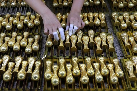 In this June 11, 2018, photo, a Chinese worker arranges the miniature FIFA World Cup trophies to process at a factory in Dongguan in south China's Guangdong province. The 21st World Cup begins on Thursday, June 14, 2018, when host Russia takes on Saudi Arabia. (Color China Photo via AP)