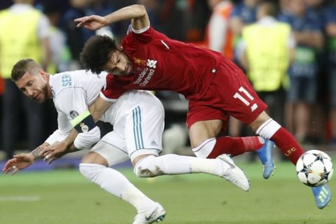 Real Madrid's Sergio Ramos, left, fouls Liverpool's Mohamed Salah during the Champions League Final soccer match between Real Madrid and Liverpool at the Olimpiyskiy Stadium in Kiev, Ukraine, Saturday, May 26, 2018. (AP Photo/Efrem Lukatsky)