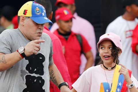 Argentina's former soccer player Diego Maradona dances with a youth during the closing campaign rally for Venezuela's President Nicolas Maduro in Caracas, Venezuela, Thursday, May 17, 2018. Maduro is seeking a new six-year mandate, and despite crippling hyperinflation and widespread shortages of food and medicine, is widely expected to win the May 20 presidential election that opponents denounce as a fraud and have been condemned by much of the international community. (AP Photo/Ariana Cubillos)