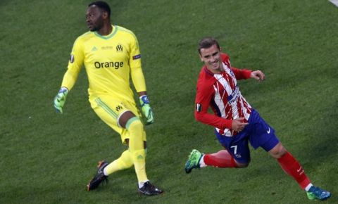 Atletico 's Antoine Griezmann, right, runs as Marseille's goalkeeper Steve Mandanda looks away after Griezmann scored his side opening goal during the Europa League Final soccer match between Marseille and Atletico Madrid at the Stade de Lyon outside Lyon, France, Wednesday, May 16, 2018. (AP Photo/Christophe Ena)