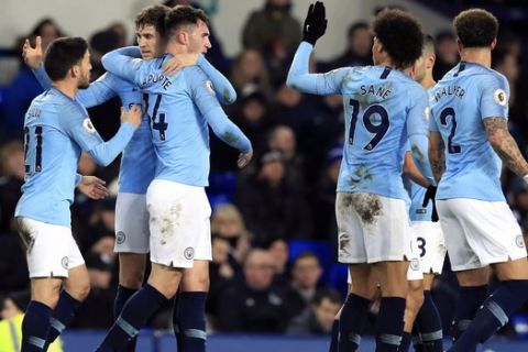 Manchester City's Aymeric Laporte, third left, celebrates scoring his side's first goal of the game with teammates during their English Premier League soccer match against Everton at Goodison Park, Liverpool, England, Wednesday, Feb. 6, 2019. (Peter Byrne/PA via AP)